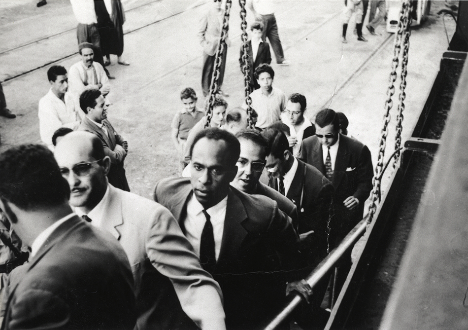 Frantz Fanon walking up a ship gangway.