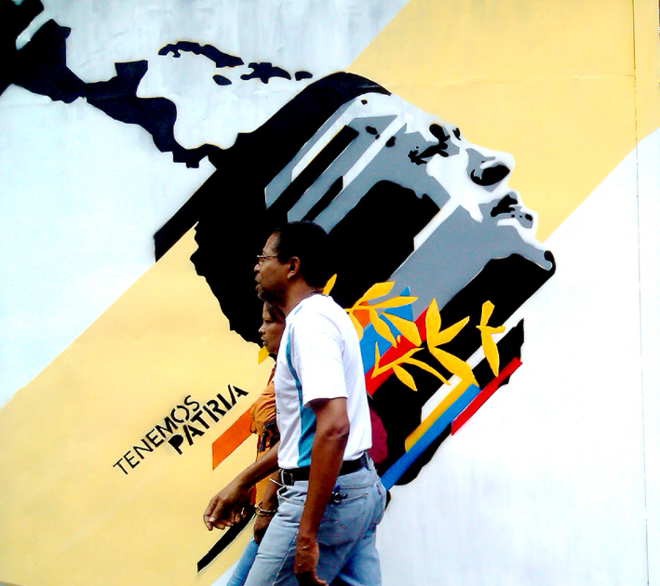 'This is our great homeland' / Tenemos Patria Grande. La Candelaria, Caracas. 2013. Passersby in front of a mural that references the vision of a free and united Latin America, following the vision of José Martí and the Bolivarian Revolution. Comando Creativo