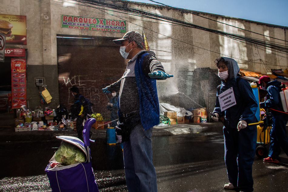 Shoppers at the market pay to be disinfected. Rodríguez Market, La Paz, Bolivia, 2020. Carlos Fiengo