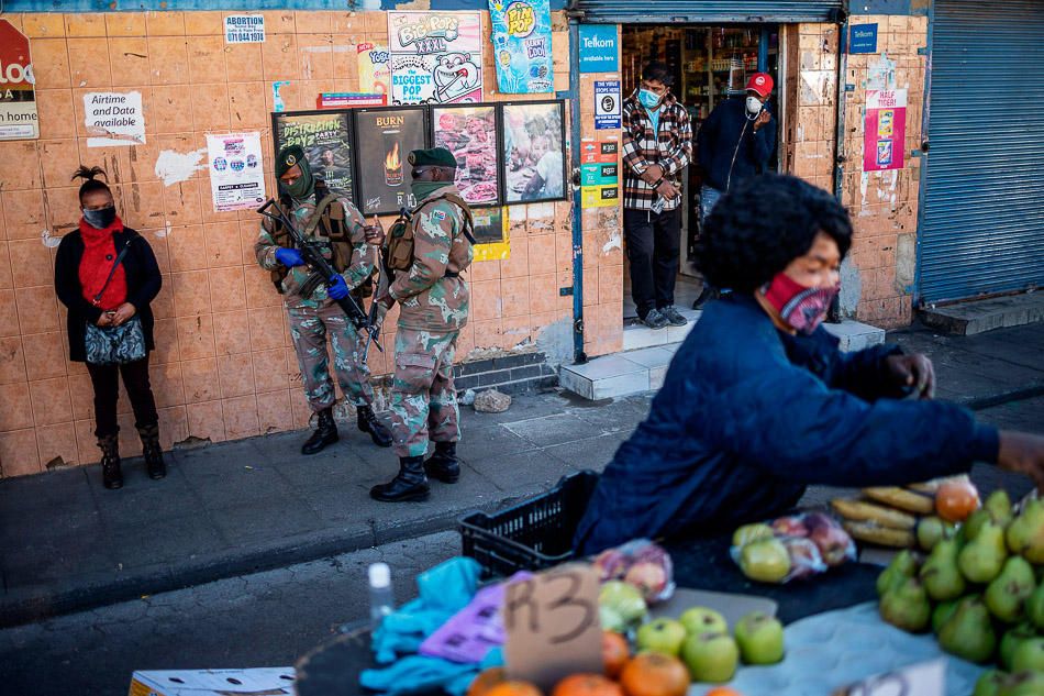 Street vendors at the Bara taxi rank during a joint patrol by the South African National Defence Force (SANDF) and the South African Police Service (SAPS) during the COVID-19 lockdown in Soweto, Johannesburg. 1 June 2020. Credit: Michelle Spatari / AFP / Getty Images