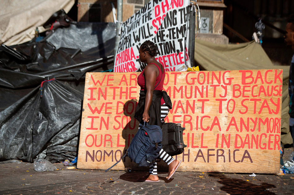 A woman walks with her belongings past a sign as hundreds of people from various African countries are evicted from the makeshift camp they are occupying around the Central Methodist Mission in Cape Town, 1 March 2020. Credit: Rodger Bosch / AFP / Getty Images