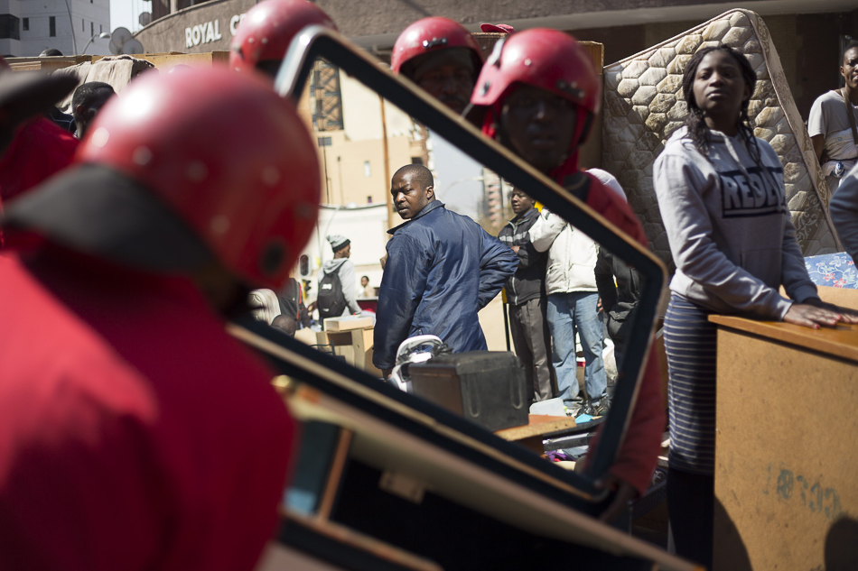 Eviction of 1,500 residents carried out by the 'Red Ants', a private security company whose name comes from the red outfits they wear during these removals, in Hillbrow, Johannesburg. 12 August 2015. Credit: Cornell Tukiri / Anadolu Agency / Getty Images