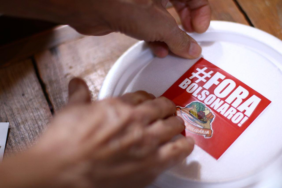 During the sixth iteration of Marmita Solidária ('Solidarity Prepared Meals') in Rio de Janeiro, 300 meals were prepared with food produced by family farms in settlements organised by the MST. In addition to solidarity, the meals carry political messages with them, such as the Fora Bolsonaro ('Out, Bolsonaro') campaign. Rio de Janeiro, Brazil, 24 August 2020. MST/RJ