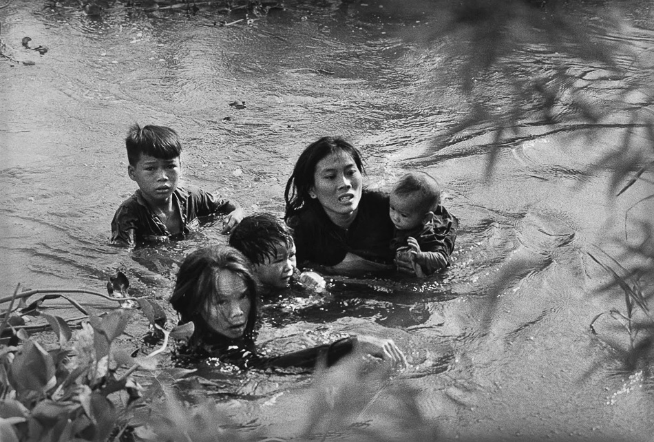 Kyōichi Sawada (Japan), A mother and her children wade across a river in Vietnam to escape US bombing, 1965.